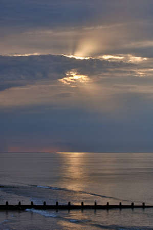 Suns rays, behind cloud, above sea, near sunset. Breakwater in foreground. HDR image.