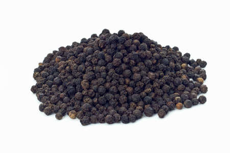 Black peppercorns on white background