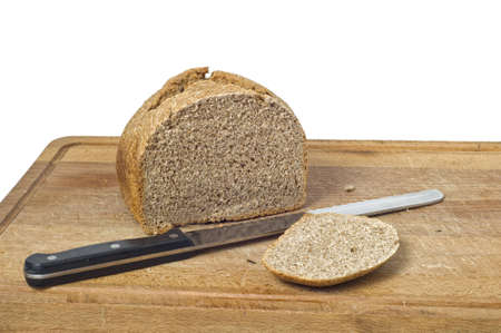A home baked wholemeal koaf with bread knife and cutting board. Isolated on white background with path.