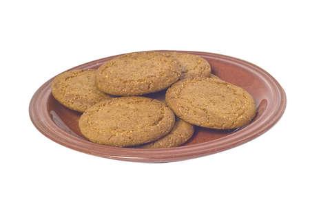 Gember Noten, koekjes op plaat tegen een witte achtergrond.