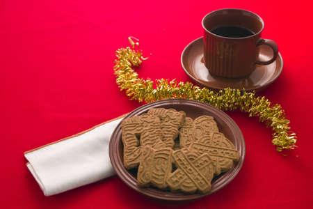 Spiced Christmas biscuits with drink in cup and saucer on red tablecloth