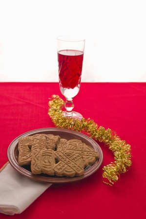 Spice Christmas biscuits on plate with wine glass on red tablecloth with white napkin. Selective focus on bisuits. Stock Photo