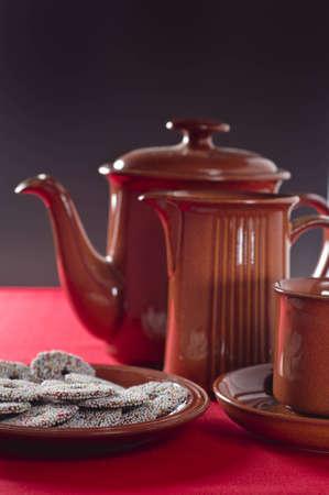 Plaat van kleine versierde koekjes, kop, schotel, melk, kruik, koffie pot