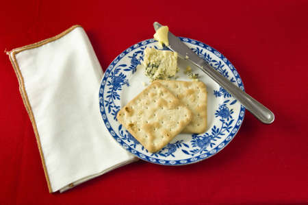 Two crackers and Stilton cheese on blue and white plate , with knife and butter. White napkin against red table cloth Stock Photo