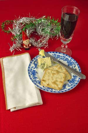 Twee crackers en Stilton kaas op blauwe en witte plaat, met mes en boter. Witte servet tegen rode tafelkleed, met decorations.Glass van rode wijn. Stockfoto