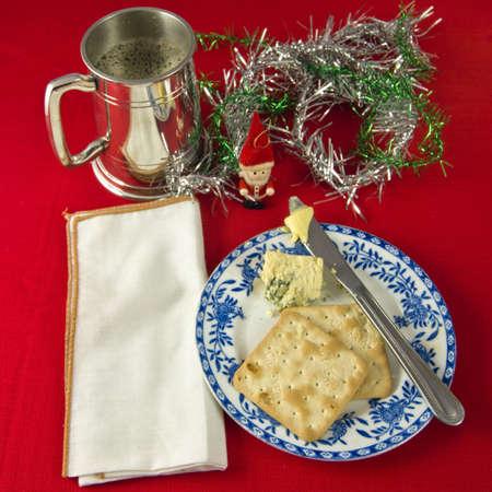 Twee crackers en Stilton kaas op blauwe en witte plaat, met mes en boter. Witte servet tegen rode tafelkleed. Pewter Tankard van bier. Kerstversiering.