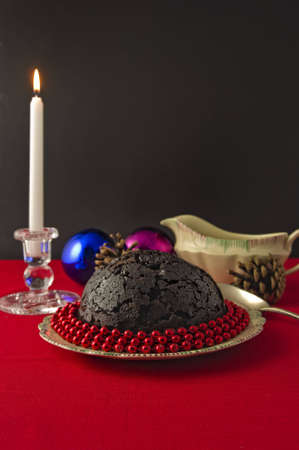 Candle lit Christmas Pudding decorated with red beads, on red tablecloth, sauce boat and pine cones, baubles and candle