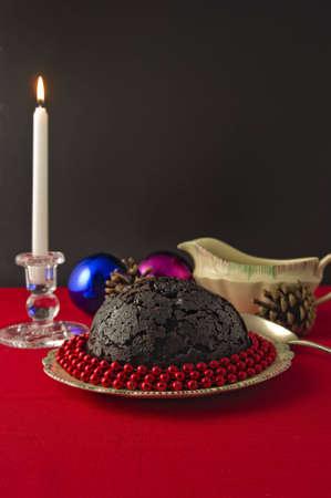 Kaars aangestoken Pudding van Kerstmis versierd met rode kralen, op rood tafelkleed, sauskom en dennenappels, kerstballen en kaars Stockfoto