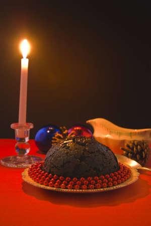 Kaars aangestoken Pudding van Kerstmis versierd met rode kralen, op rood tafelkleed, sauskom en dennenappels, kerstballen en kaarsen. Warm evenwichtig voor het effect.
