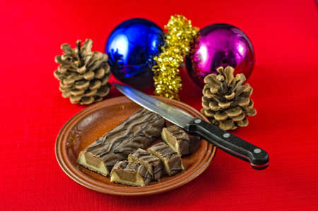 Christmas treat, chocolate covered marzipan and nougat, bar, partly cut on plate on red tablecloth. hristmas decorations on table. Selective focus on chocolate bar. Stock Photo