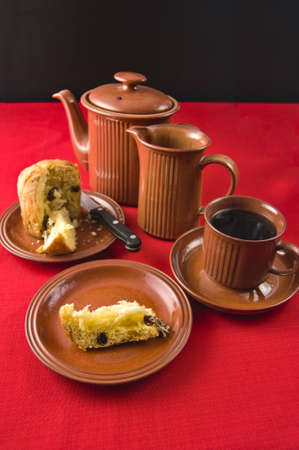 Miniature Panatone cut, with slice and separate plate, cup of coffee, milk and coffee jugs on red tablecloth