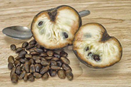 Custard apple, also known as Bullocks or Bulls Heart  Cut on wooden chopping board with seeds and spoon