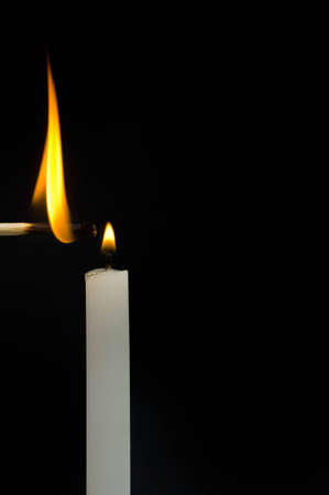 Flaming match and candle on black with room for text Stock Photo