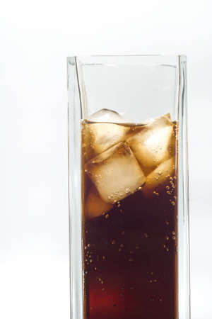 Tall glas of iced cola on white background