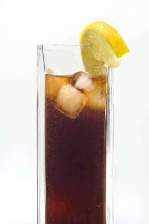 Tall glass of cola with lemon and ice cubes