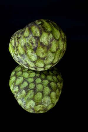 Custard appel, ook wel bekend als Bullocks of Bulls Hart Op zwart met reflectie