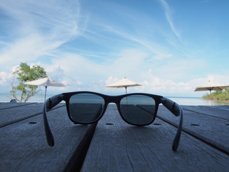 disrupted: Black sunglasses Placed on a wooden board at the beach on Disrupted clouds background.