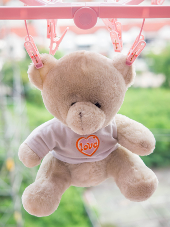 love hurts: Hanging teddy bear Light brown dried in the sun  on blur background. The  teddy bear doll with orange heart and love message on a white shirt. The  teddy bear doll can be the communication of love.