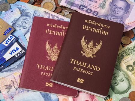 tarjeta visa: Pasaporte, billetes de dinero y la tarjeta Visa en la pila de monedas de la moneda baht.