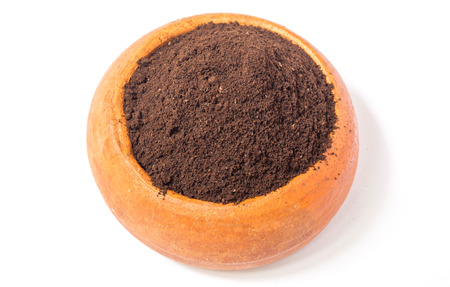 coffee grounds: Coffee grounds in a brown pottery cup on white background.
