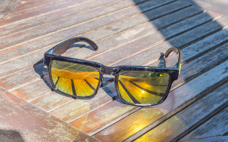 Sunglasses yellow Mirror glasses reflective light put on the wooden table with shadow of tree. Stock Photo