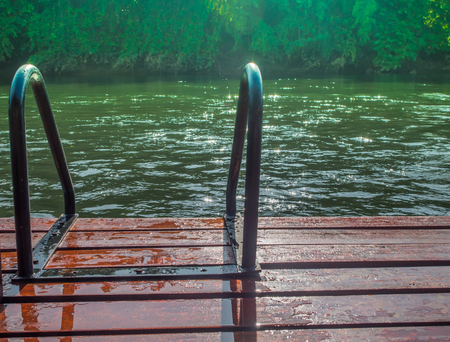 rivulet: Green river with teak wood flooring stripes summer vacation. Stock Photo