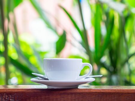 Close up white espresso coffee cup put on the wooden table in cafe shop with natural background orange light fillers.