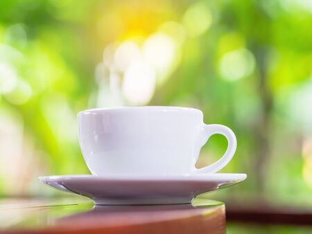 Close up white coffee cup put on the wooden table in cafe shop with natural background orange light fillers. Stok Fotoğraf