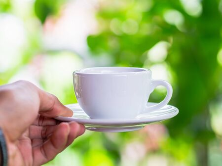 Close up hand Pick white coffee cup on blur green color nature background in the cafe shop morning with orange filters.