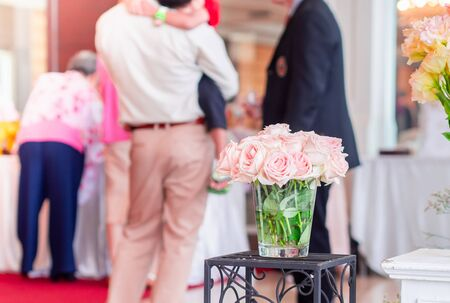 Close up pink rose flowers on blur  associate people background In vase glass bottle wedding day.