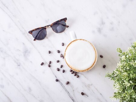 Top view of hot Cappuccino in the white cup ,coffee bean and black sunglasses put on the fabric and marble table in cafe morning work day background.