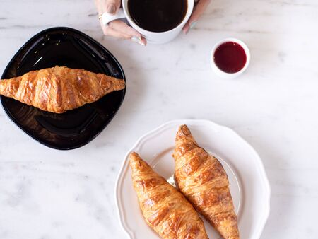 Top view women hands hold a hot coffee cup, croissant put on the white marble table in cafe shop with nature lighting background.