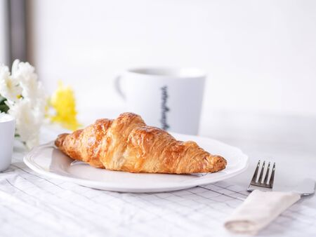 Breakfast with cup of hot coffee and brown croissant in the plate put on white marble table in the cafe Stok Fotoğraf