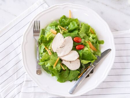Concept of green vegetarian and chicken diet. Fresh leaves , red tomato, carrot and different Vegetable salads in the dish put on the table morning background.Love health concept