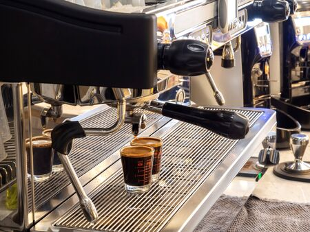 coffee extraction from professional prepared coffee machine with bottomless in cafe shop background. Stok Fotoğraf