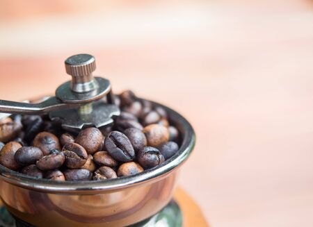 Close up coffee beans organic in wooden grinder homemade on wood table background, top view Stock Photo