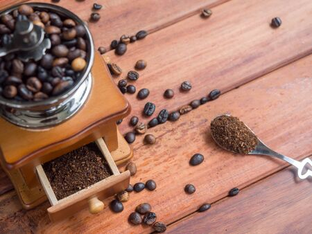 Close up coffee beans organic in wooden grinder homemade on wood table background, top view and Focus on Coffee powder Stock Photo