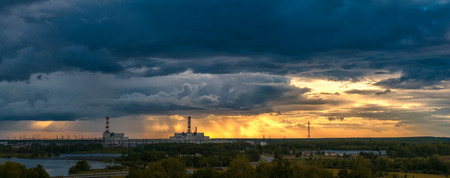 panorama of great sunset above power plant summer evening