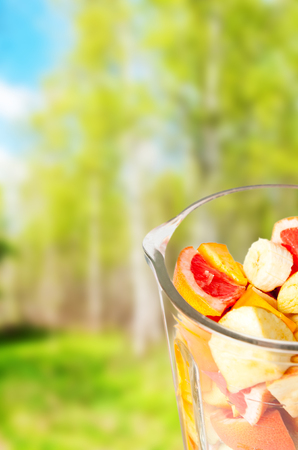 Sliced Fruits arranged in plastic cup with spring green background
