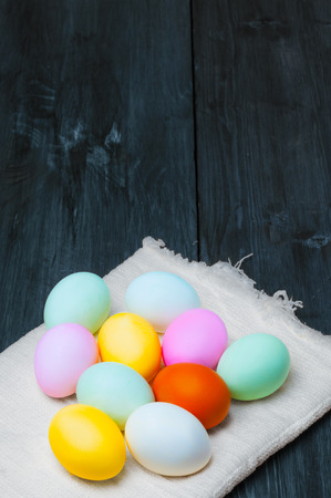 Colorful Easter eggs on towel on old rustic wooden background Standard-Bild