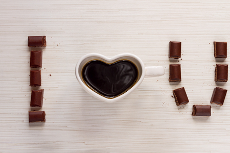 valentine day cup of coffee: Cup with coffee shaped heart i love you and valentines chocolate on wood background Stock Photo