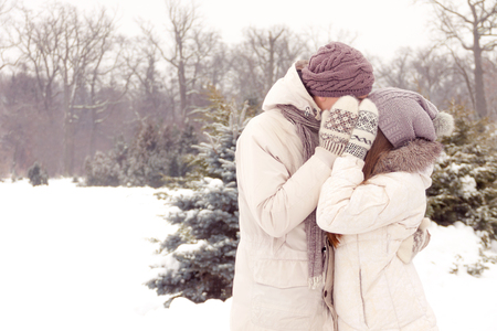 Happy couple in love kissing and hiding faces by hands in mittens in park in winter