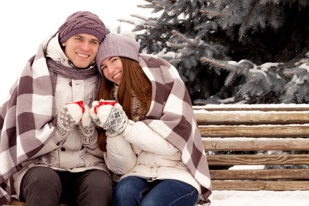 outerwear: Happy couple in love in white outerwear siting and drink coffee in park in winter
