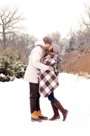 Joyful romantic couple kissing in park in winter 스톡 콘텐츠