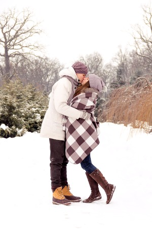 Joyful romantic couple kissing in park in winter Stock Photo