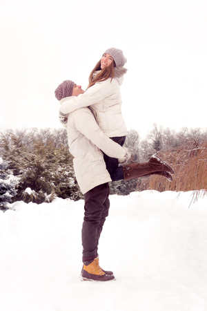 outerwear: Happy couple in love in white outerwear fool around in park in winter