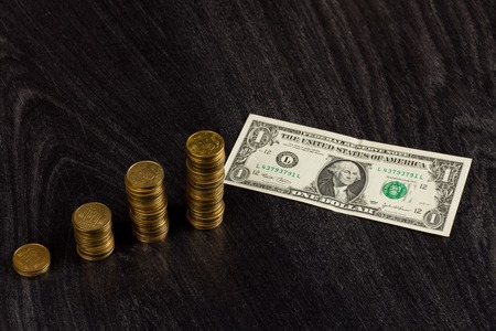 crisis economica: Economic crisis concept. Gold ukrainian stacks of coins and american one dollar on wooden background