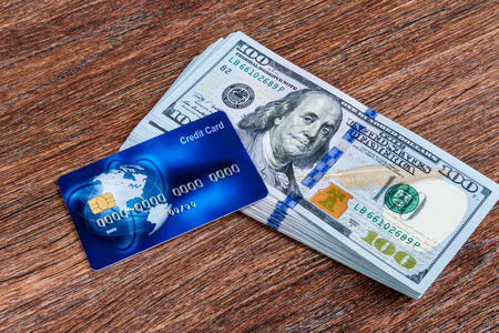 one hundred dollars: Blue credit card on one hundred dollars