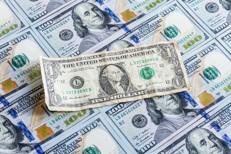 deprecated: old crumpled dollar bills lying on the new hundred dollar bills