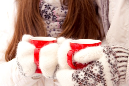 outerwear: Romantic young couple in love in white outerwear drink coffee from red cups in park in winter Stock Photo